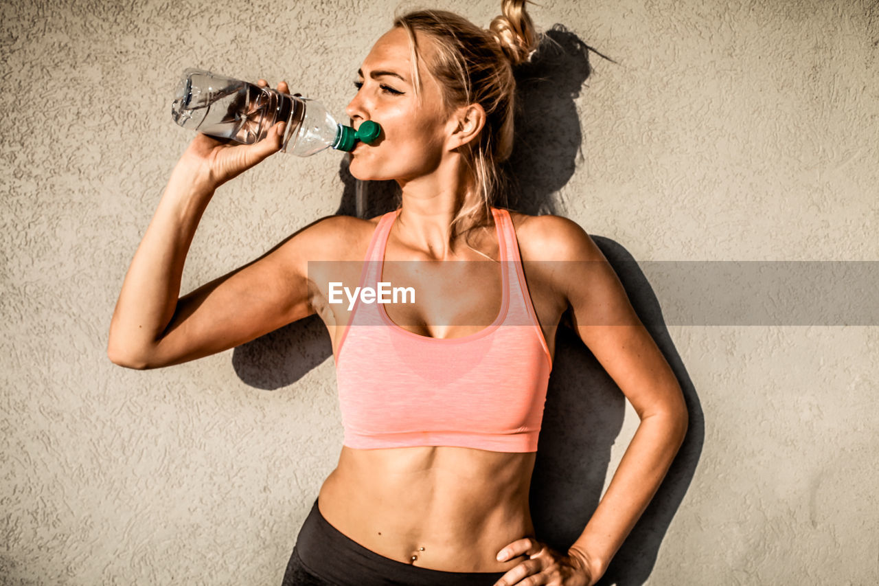 Woman drinking water against wall