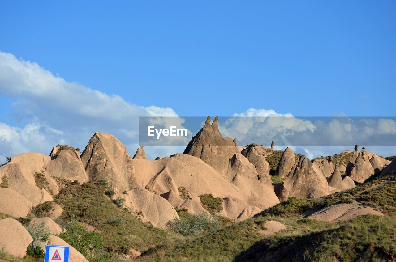 Scenic View Of Rock Formations Against Cloudy Sky