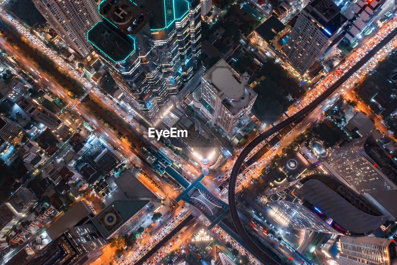 HIGH ANGLE VIEW OF ILLUMINATED CITY STREET AND BUILDINGS