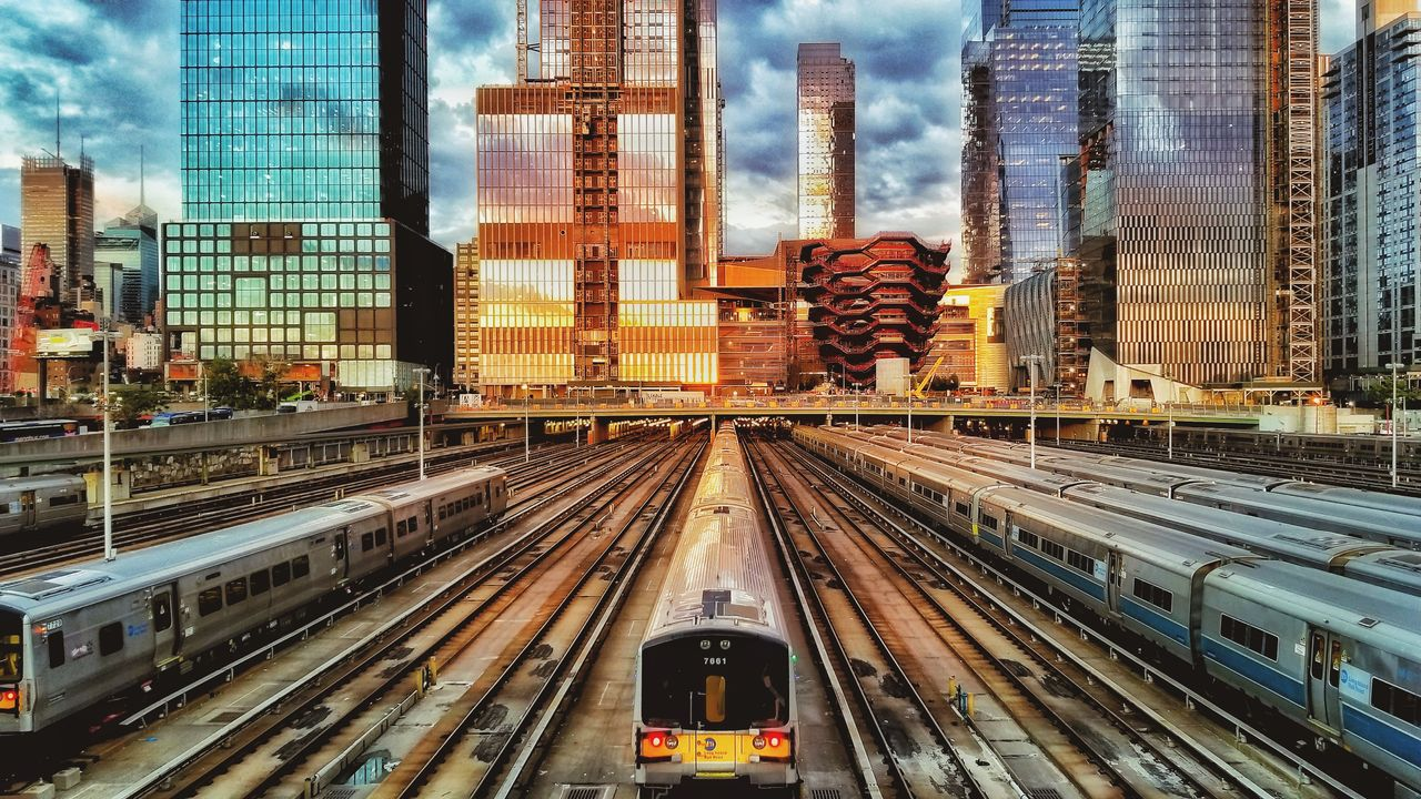building exterior, architecture, built structure, city, transportation, office building exterior, mode of transportation, rail transportation, railroad track, public transportation, track, skyscraper, train, sky, building, no people, train - vehicle, day, travel, office, outdoors, cityscape, modern, financial district