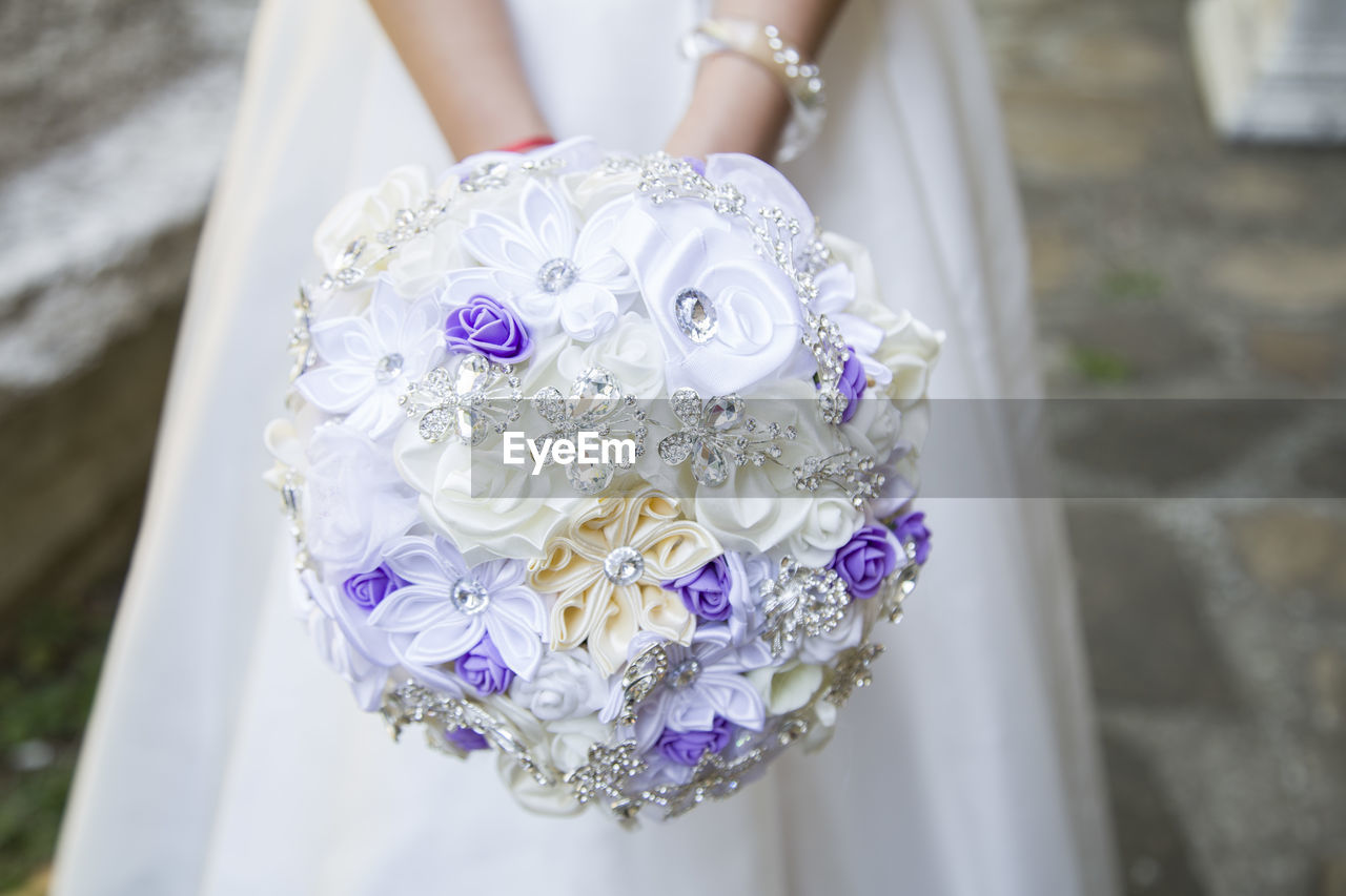 Midsection of bride holding bouquet while standing in wedding ceremony