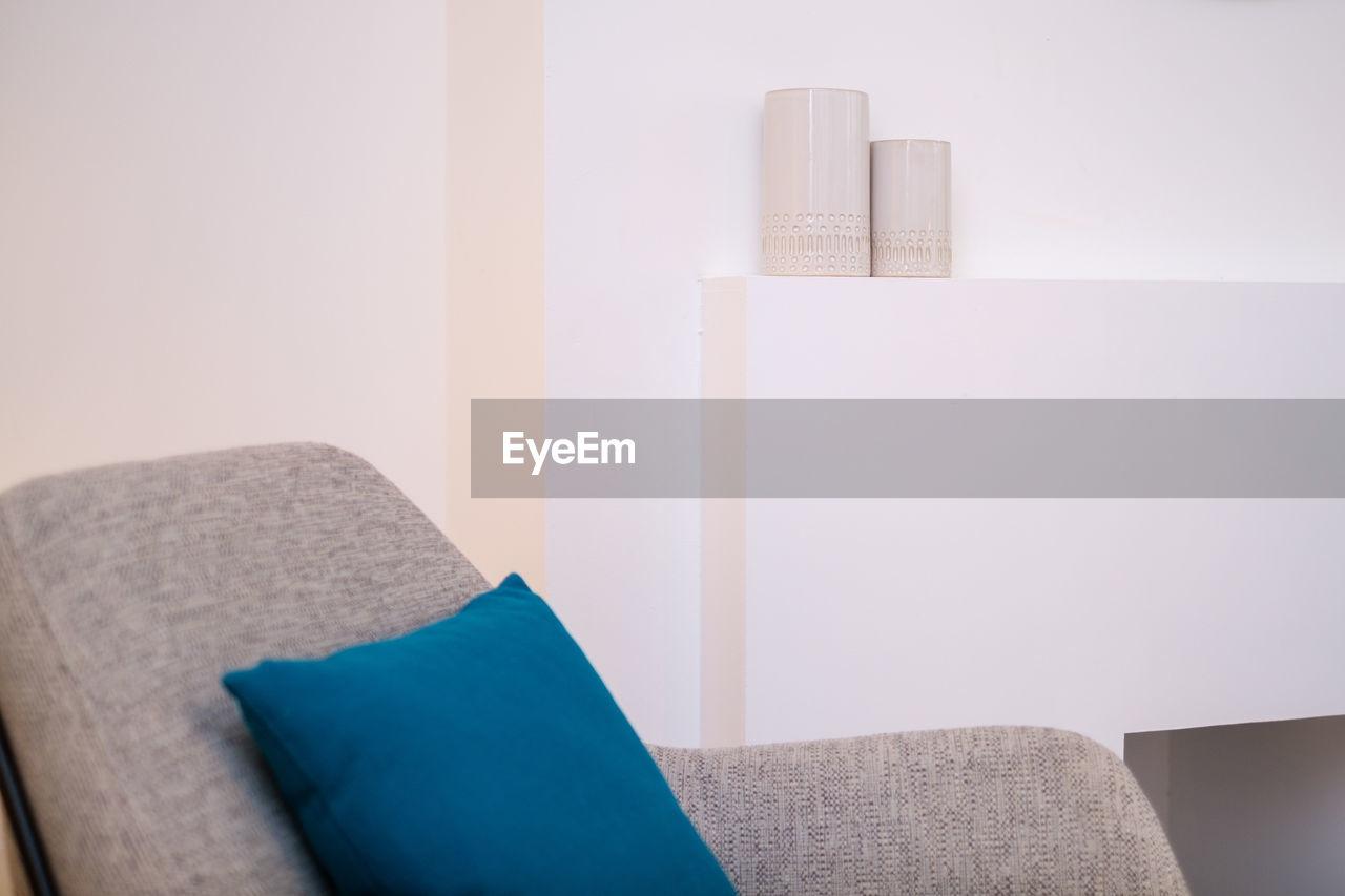 Cushion on armchair against wall at home