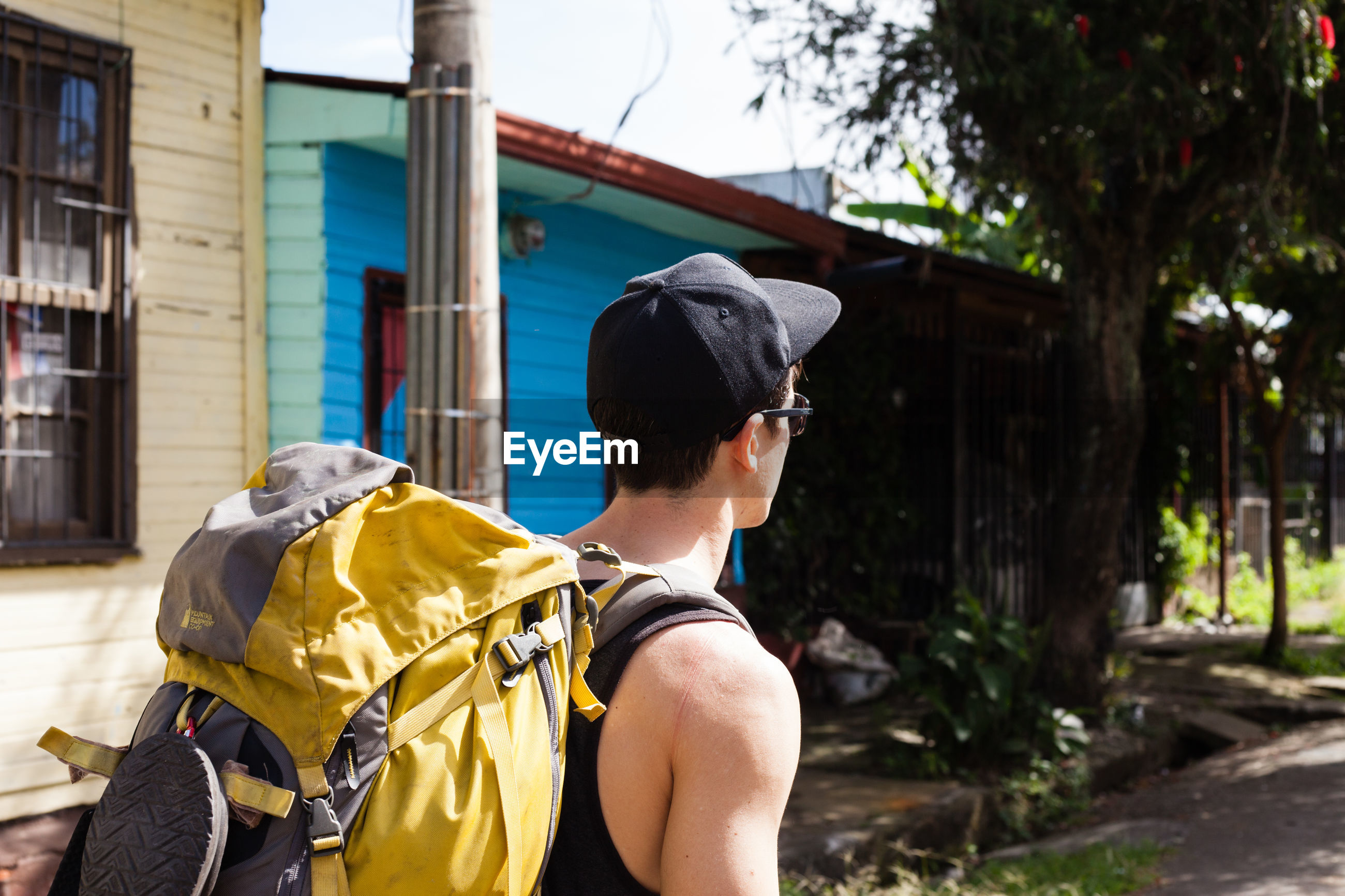 Side view of young man with backpack walking on road against house