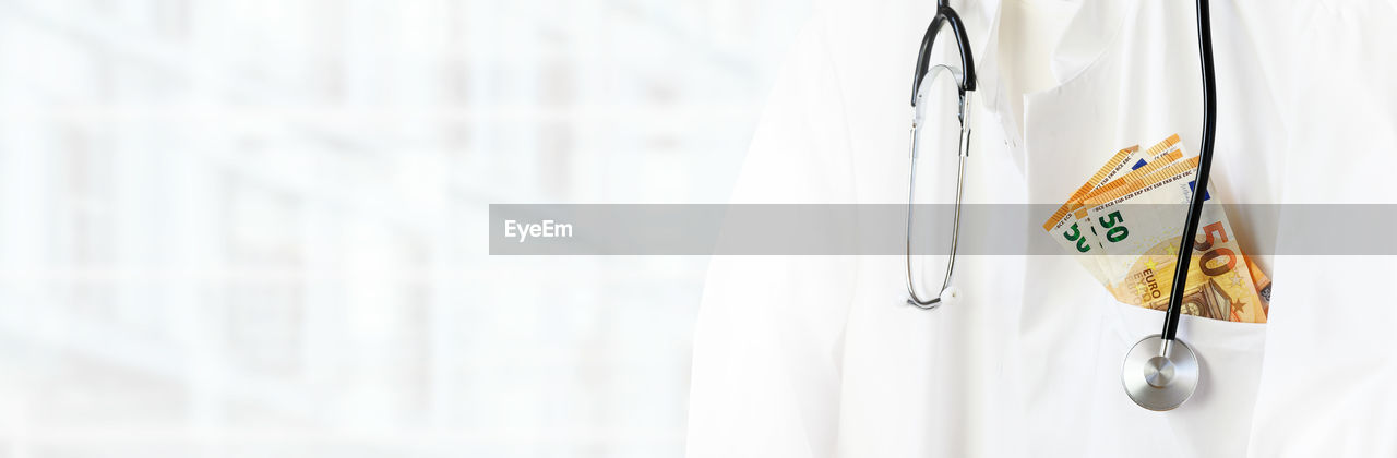 white color, no people, close-up, hanging, focus on foreground, indoors, copy space, clothing, selective focus, paper, in a row, panoramic, day, wood - material, healthcare and medicine, lab coat, architecture, safety, metal, clean