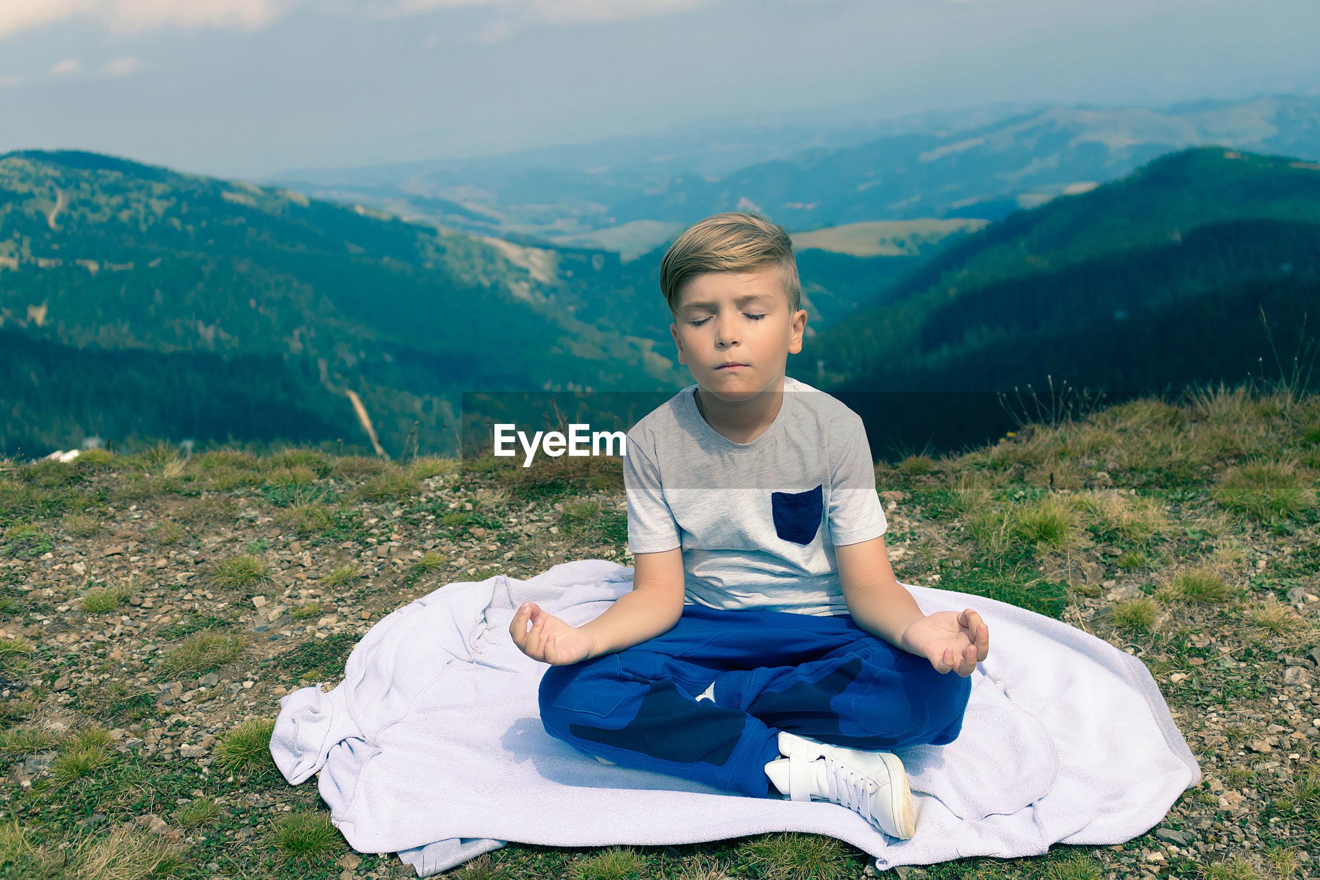BOY SITTING ON FIELD AGAINST MOUNTAIN