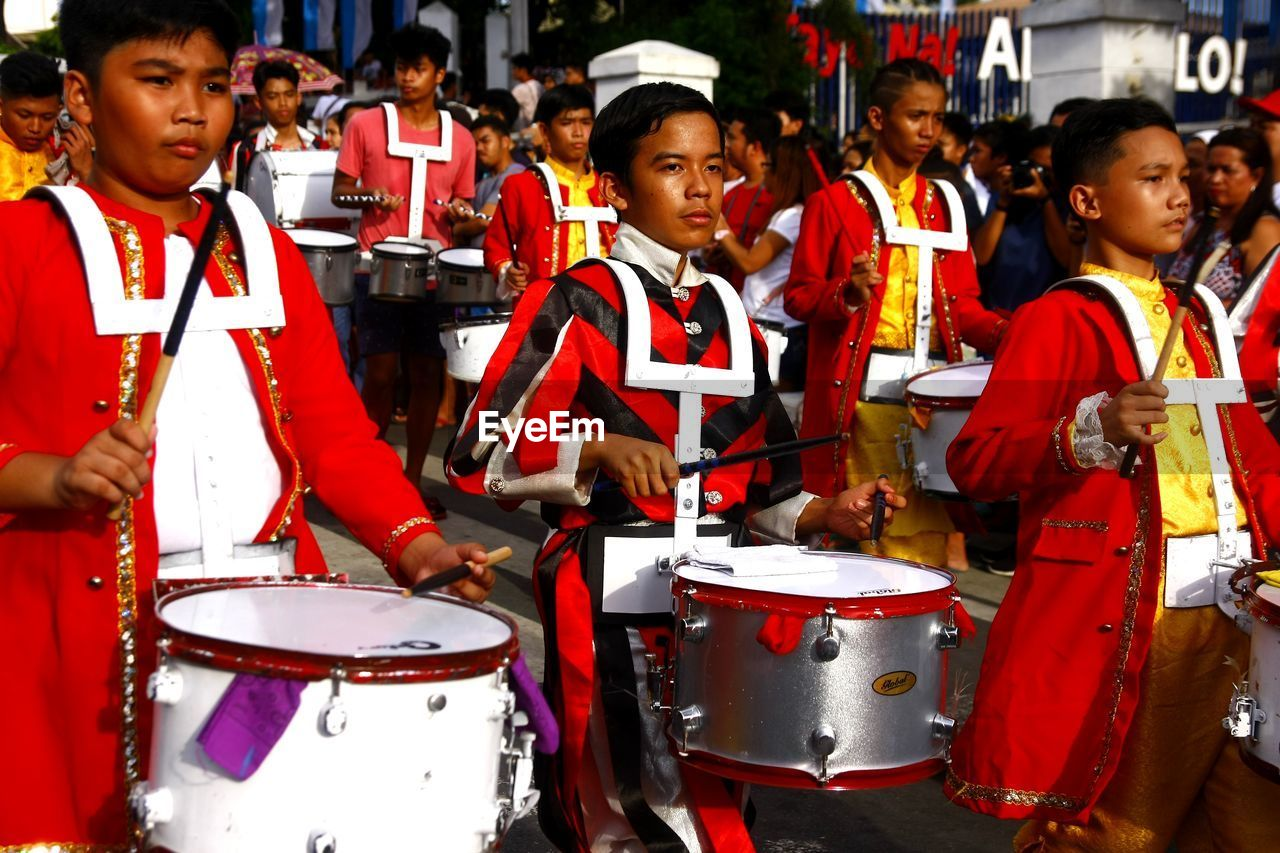 drum - percussion instrument, group of people, men, music, musical instrument, musical equipment, arts culture and entertainment, drummer, musician, real people, playing, red, people, artist, occupation, drumstick, performance, drum, percussion instrument, adult