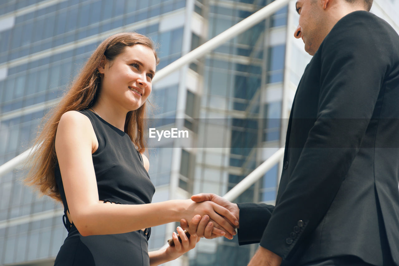 Low angle view of business couple doing handshake while standing in city