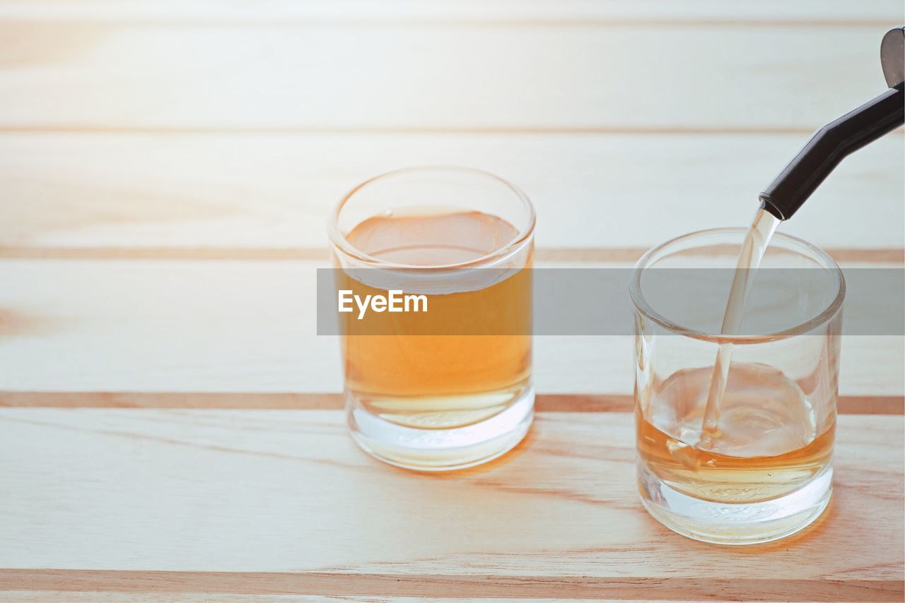 drink, refreshment, glass, table, drinking glass, household equipment, food and drink, still life, indoors, glass - material, wood - material, no people, freshness, water, transparent, close-up, focus on foreground, food, high angle view, non-alcoholic beverage, wood grain, tea cup
