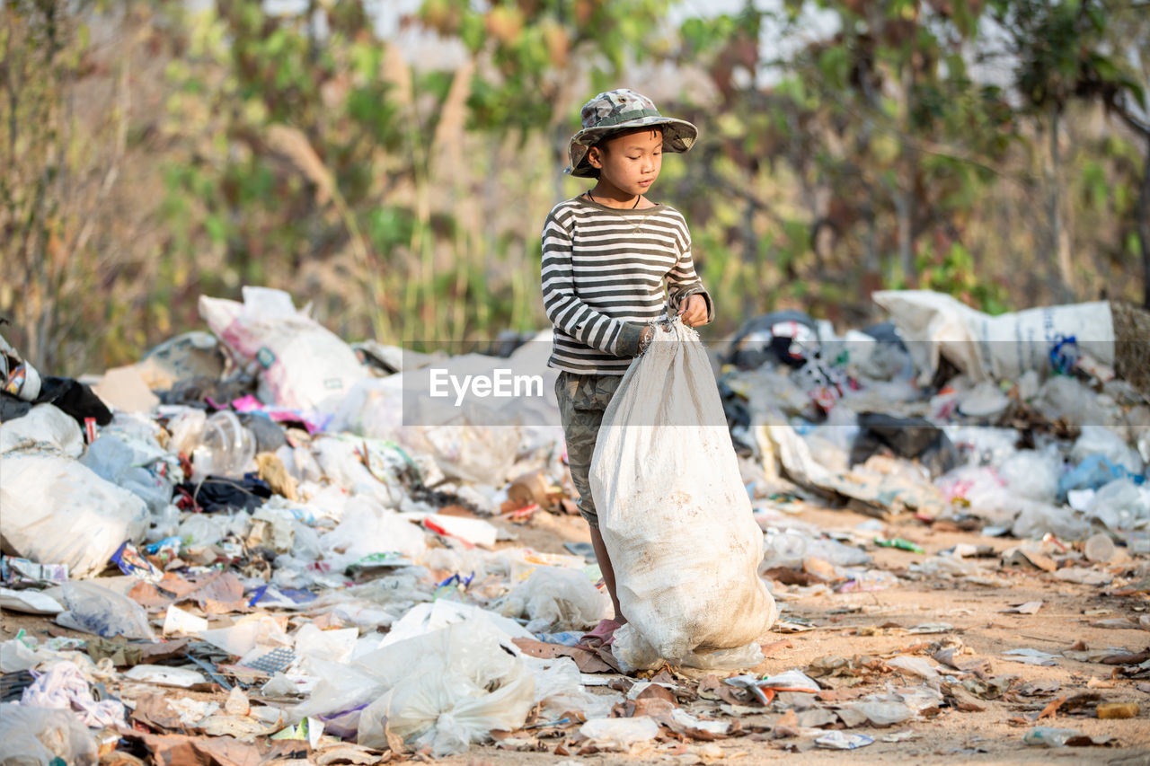 Full length of man standing on garbage