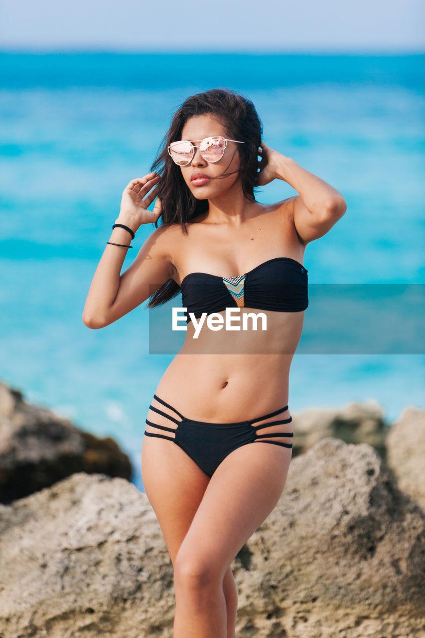 Woman in bikini and sunglasses standing at beach
