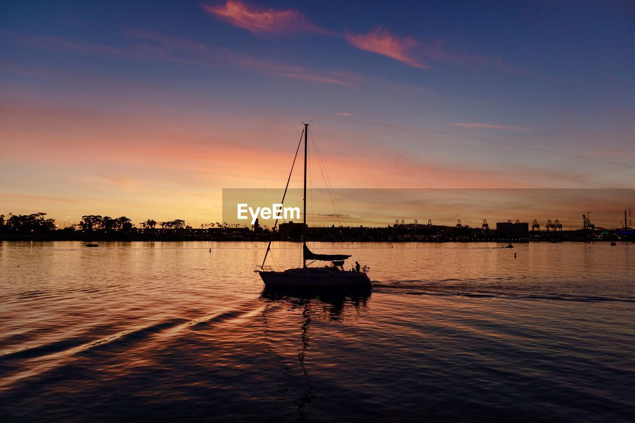 water, sunset, nautical vessel, sky, transportation, mode of transportation, waterfront, cloud - sky, silhouette, beauty in nature, orange color, scenics - nature, reflection, tranquility, tranquil scene, nature, sailboat, sea, idyllic, outdoors