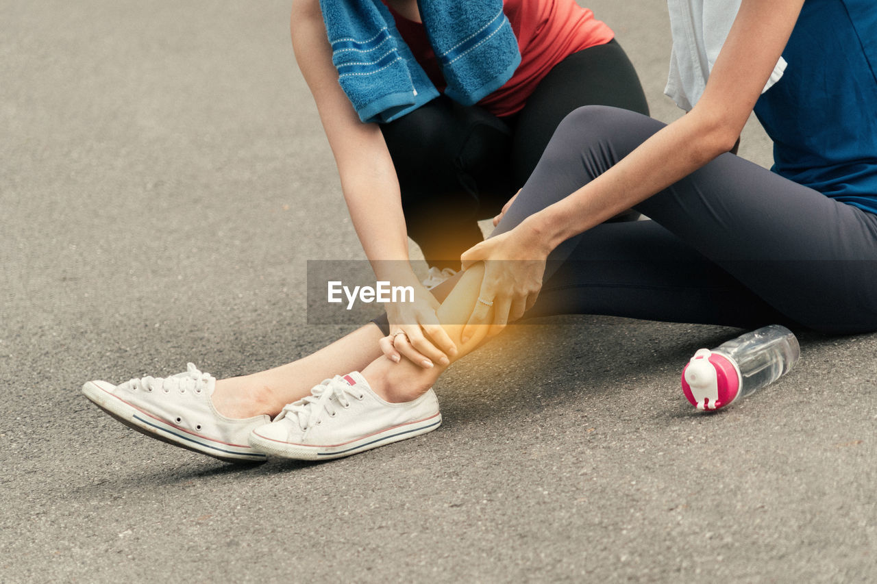 Low Section Of Woman Adjusting Friend Leg On Road