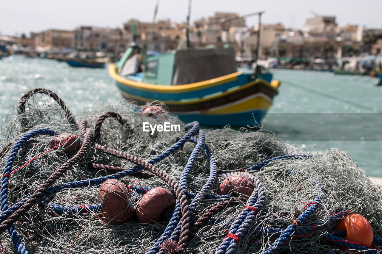 nautical vessel, water, rope, fishing net, transportation, fishing, harbor, moored, mode of transportation, fishing industry, focus on foreground, nature, sea, day, commercial fishing net, buoy, no people, pier, fishing rod, outdoors, fishing boat, complexity