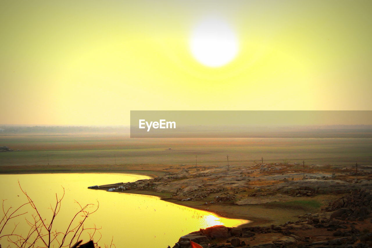 scenics, sky, tranquility, nature, beauty in nature, tranquil scene, sun, outdoors, landscape, no people, clear sky, sunset, water, yellow, day