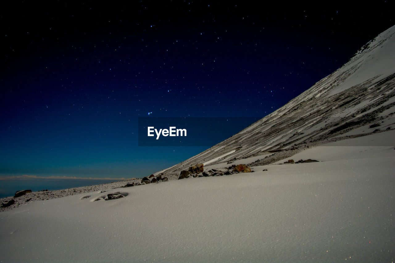 Scenic View Of Snowy Mountain Against Starry Sky