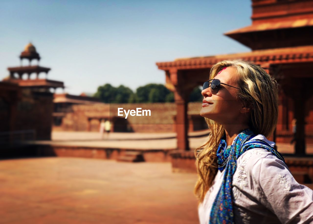 Side view of young woman wearing sunglasses at historic building