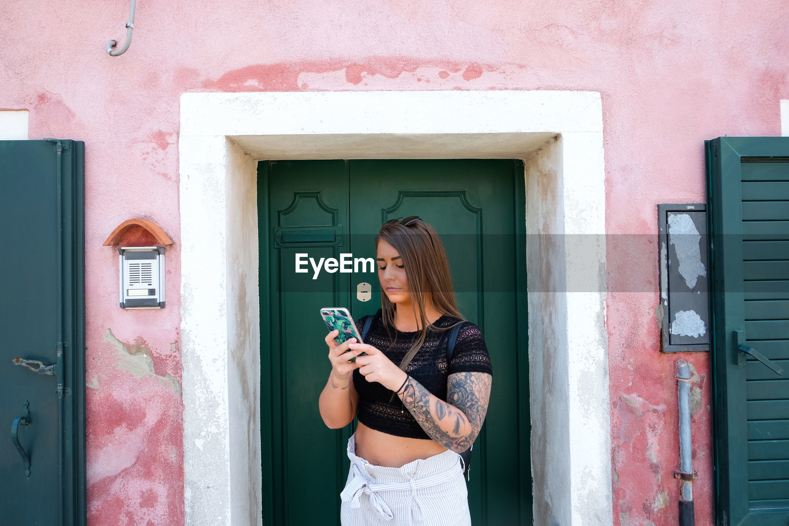 Young woman using phone while standing against door