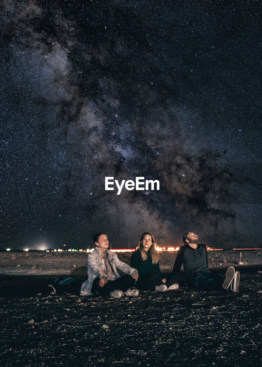 Friends Sitting On Field Against Star Field At Night