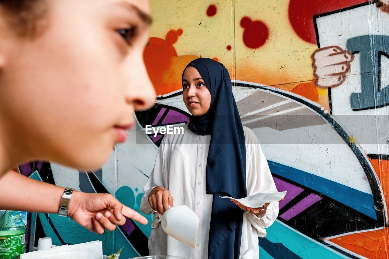 PORTRAIT OF A BEAUTIFUL YOUNG WOMAN STANDING AGAINST GRAFFITI WALL