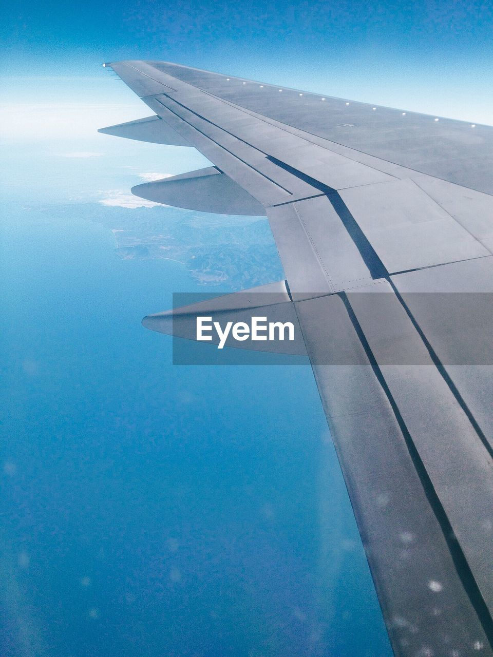 Cropped Image Of Airplane Over Blue Sea