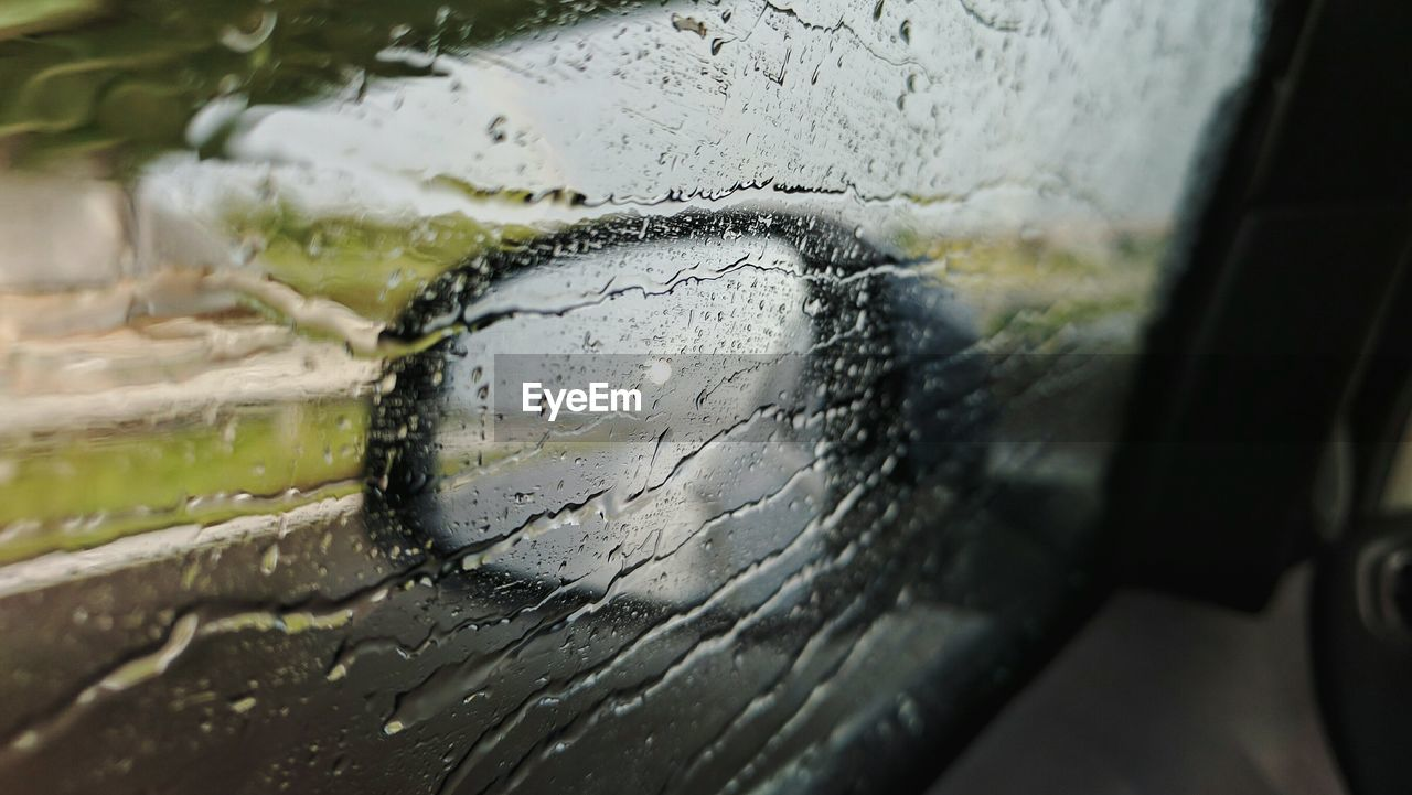 Side-View Mirror Seen Through Wet Glass Window