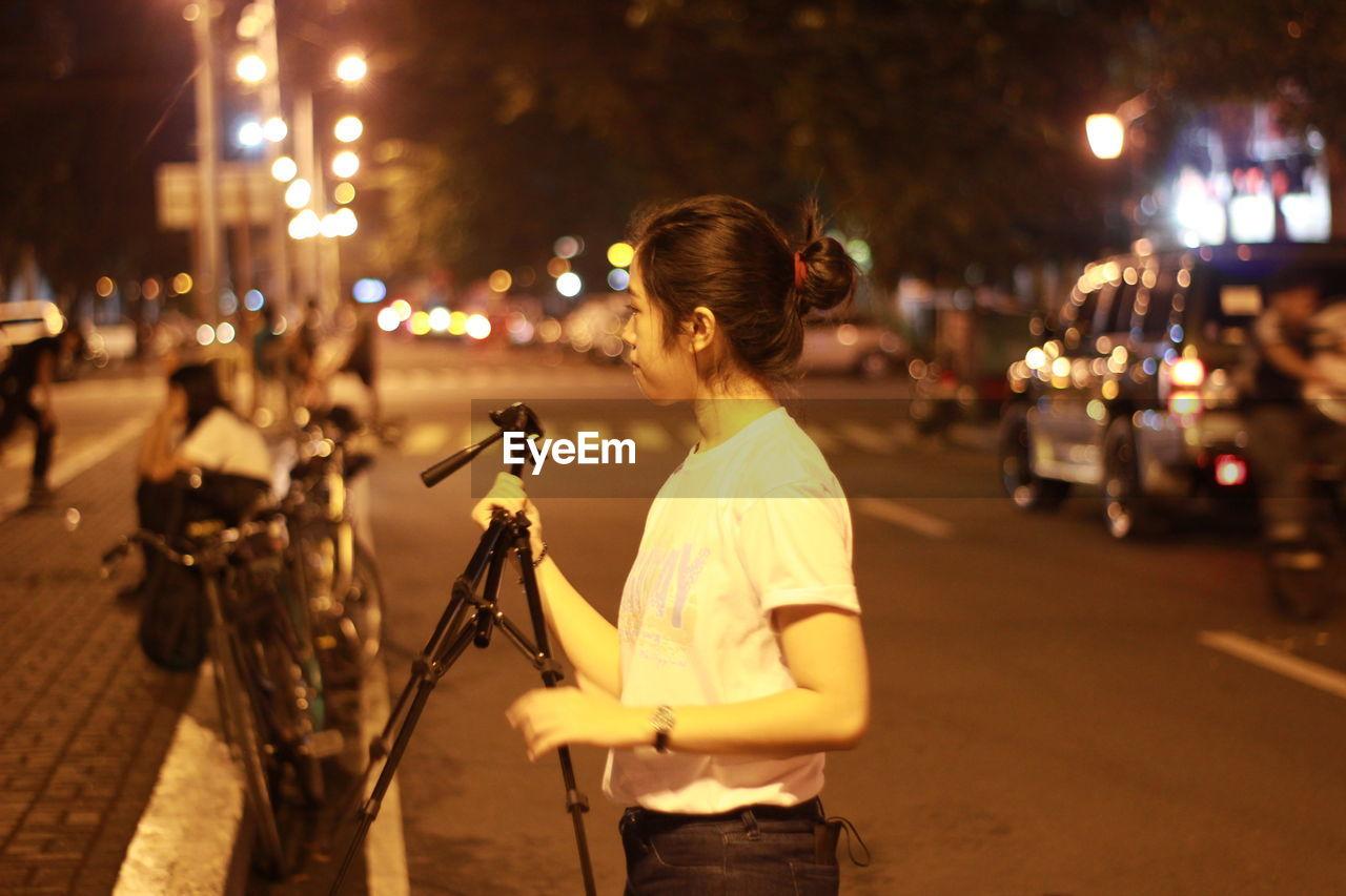 Young Woman Holding Tripod On Illuminated Street At Night