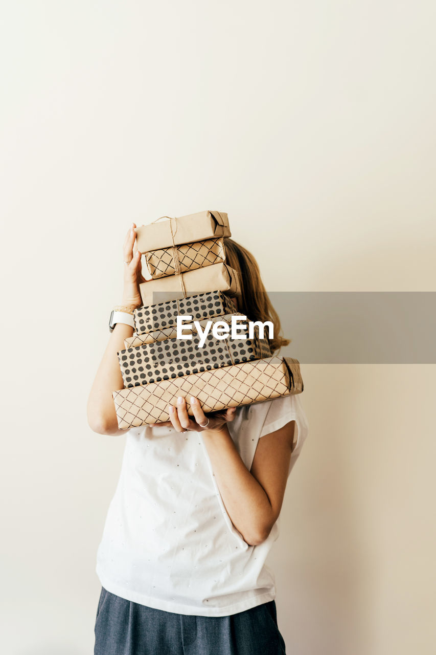 Young cheerful female holds a stack of gift boxes packed in craft paper and hides behind them.