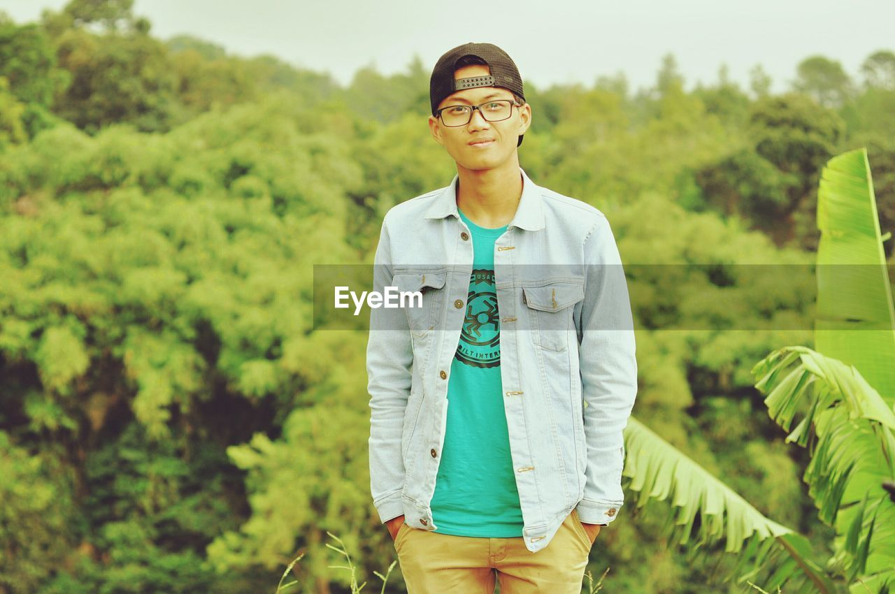 eyeglasses, front view, real people, one person, focus on foreground, green color, standing, portrait, young adult, looking at camera, young men, casual clothing, field, tree, nature, day, outdoors, lifestyles, leisure activity, growth, smiling, happiness, young women