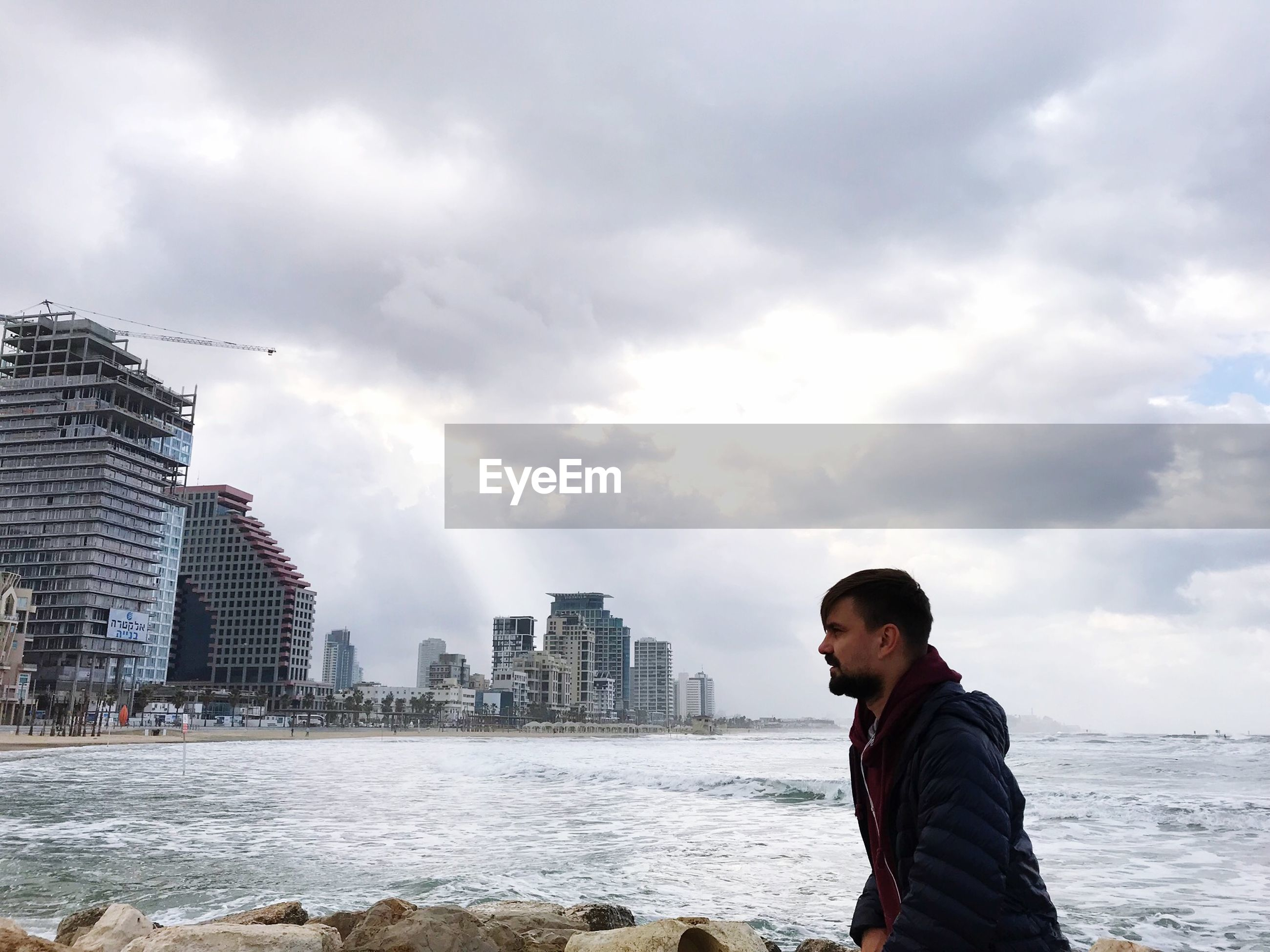 Man at beach in city against sky