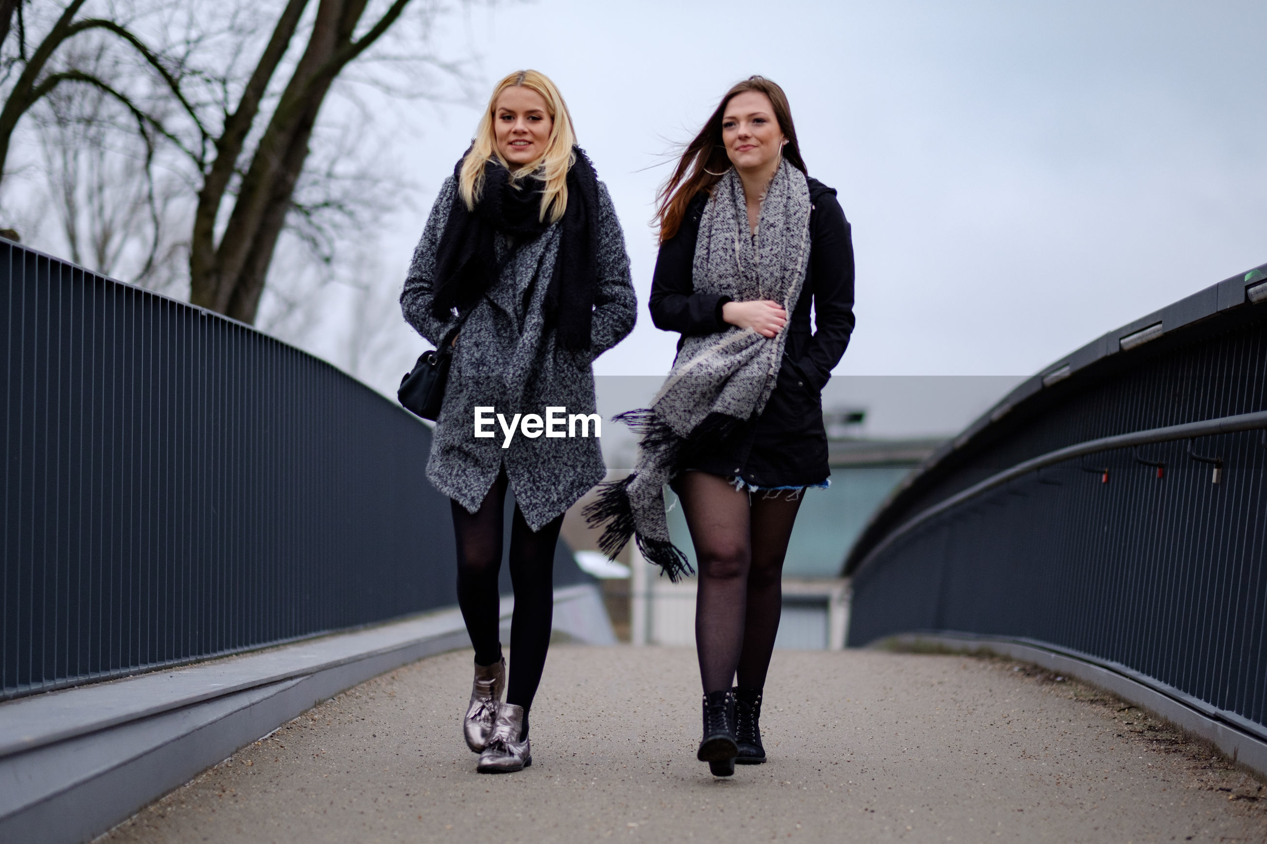 Young women walking on footbridge against sky