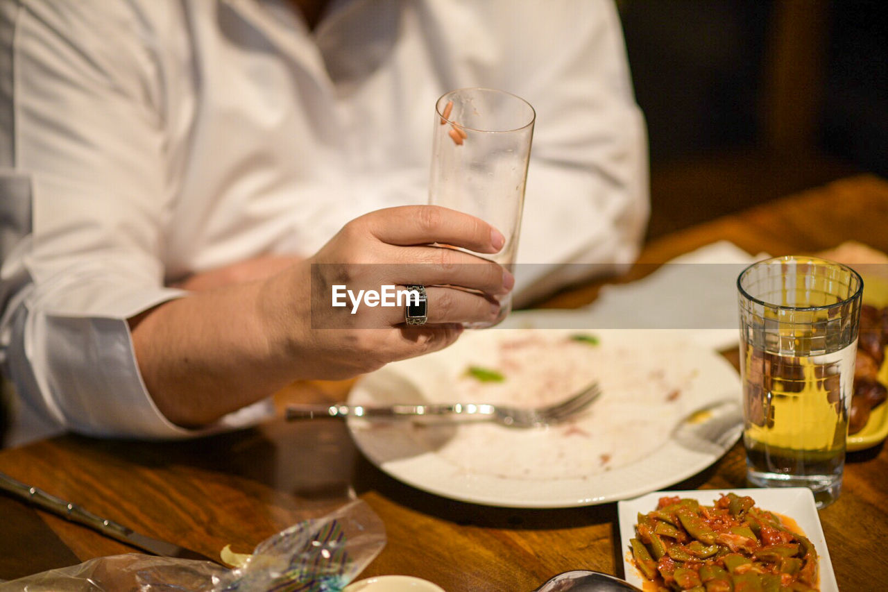 real people, food and drink, table, indoors, holding, midsection, one person, freshness, food, men, human hand, hand, refreshment, drink, glass, alcohol, drinking glass, occupation, focus on foreground, household equipment, chef