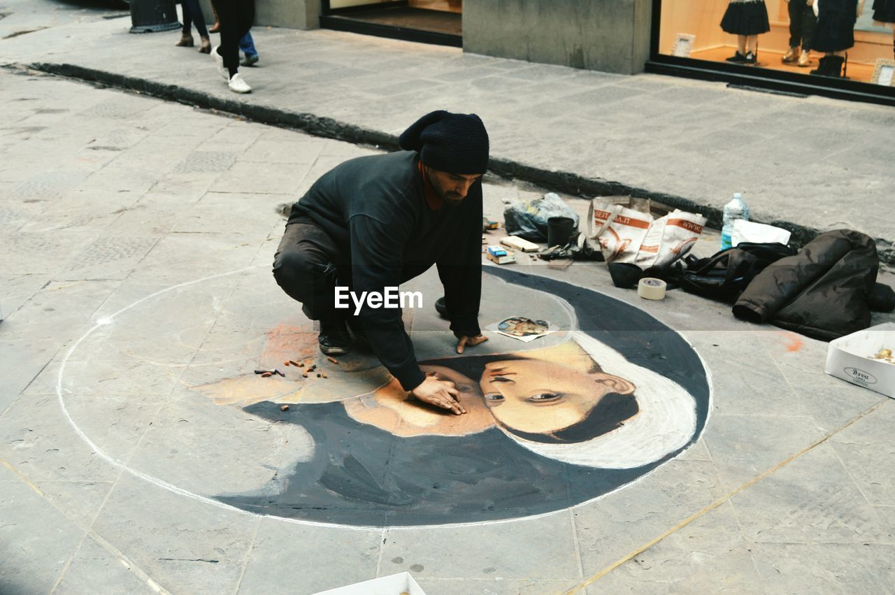 FULL LENGTH OF MAN WITH UMBRELLA ON STREET