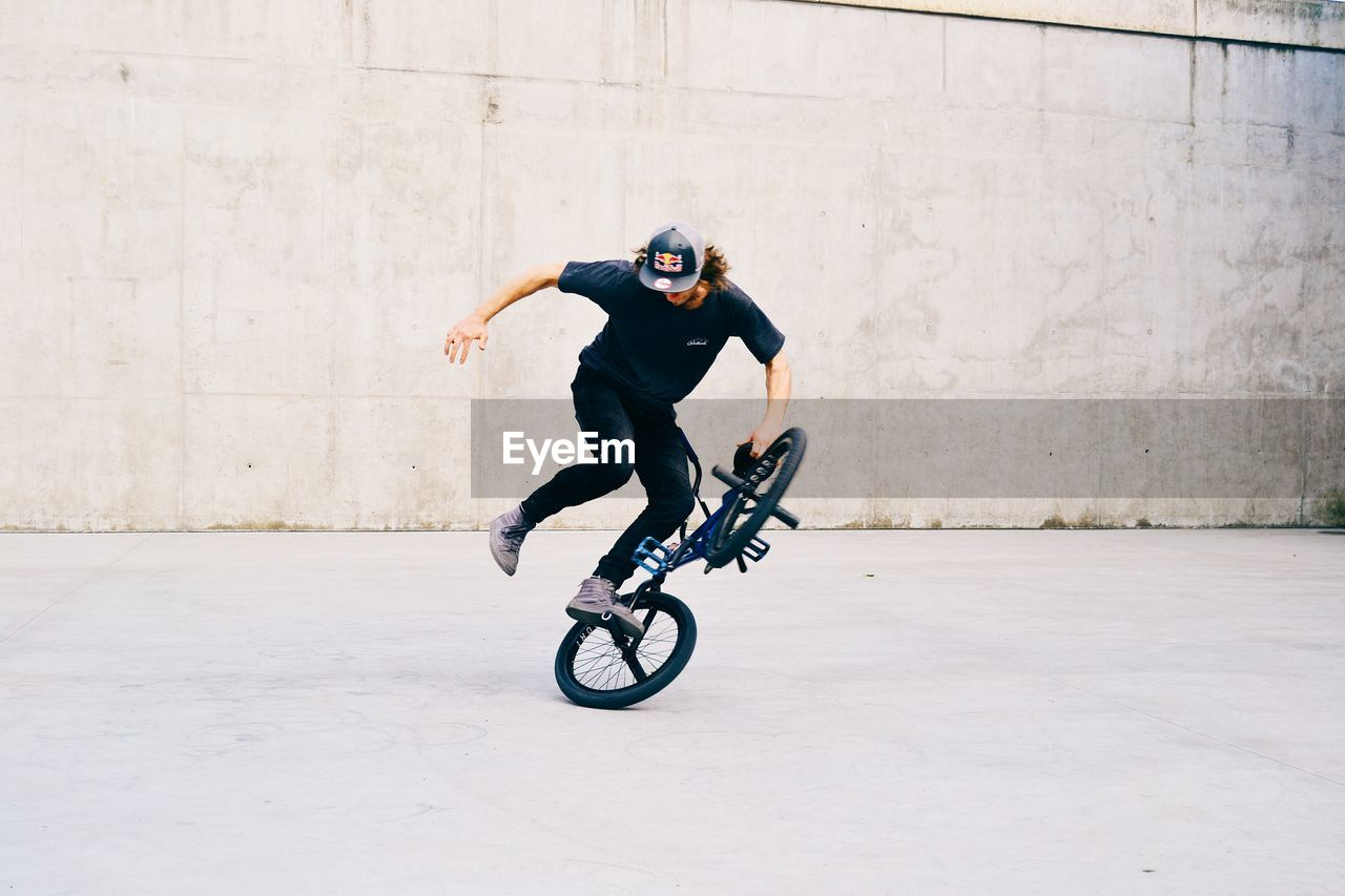 FULL LENGTH OF MAN RIDING BICYCLE ON MOTORCYCLE