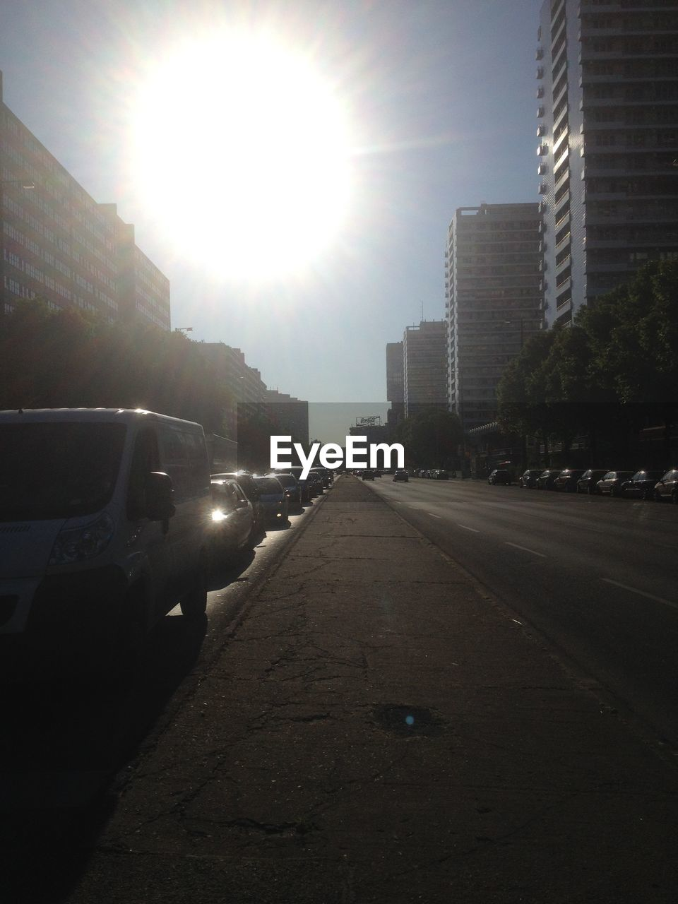 sun, sunlight, sunbeam, lens flare, car, building exterior, land vehicle, architecture, road, built structure, skyscraper, transportation, street, city, no people, the way forward, day, sky, cityscape, outdoors