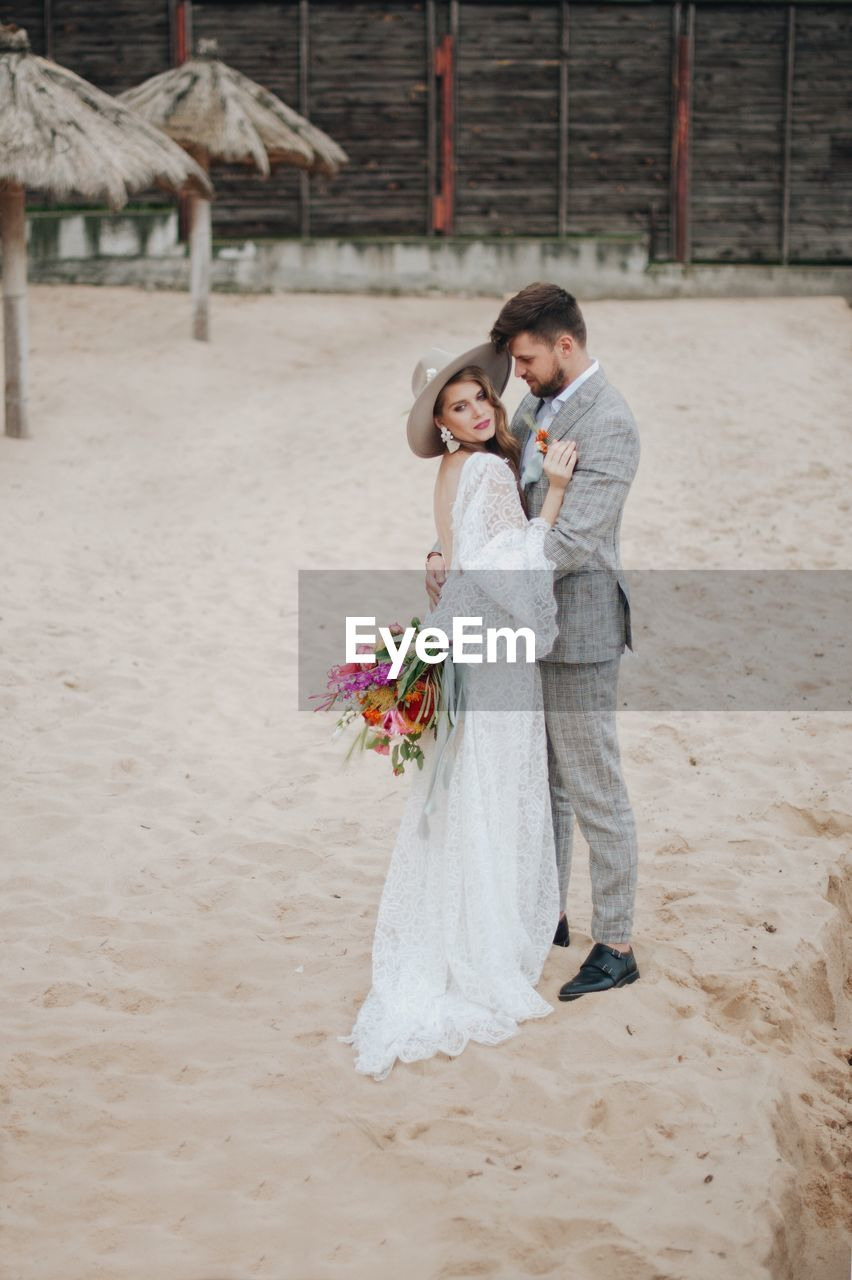 Bride And Bridegroom Standing At Beach During Wedding Ceremony