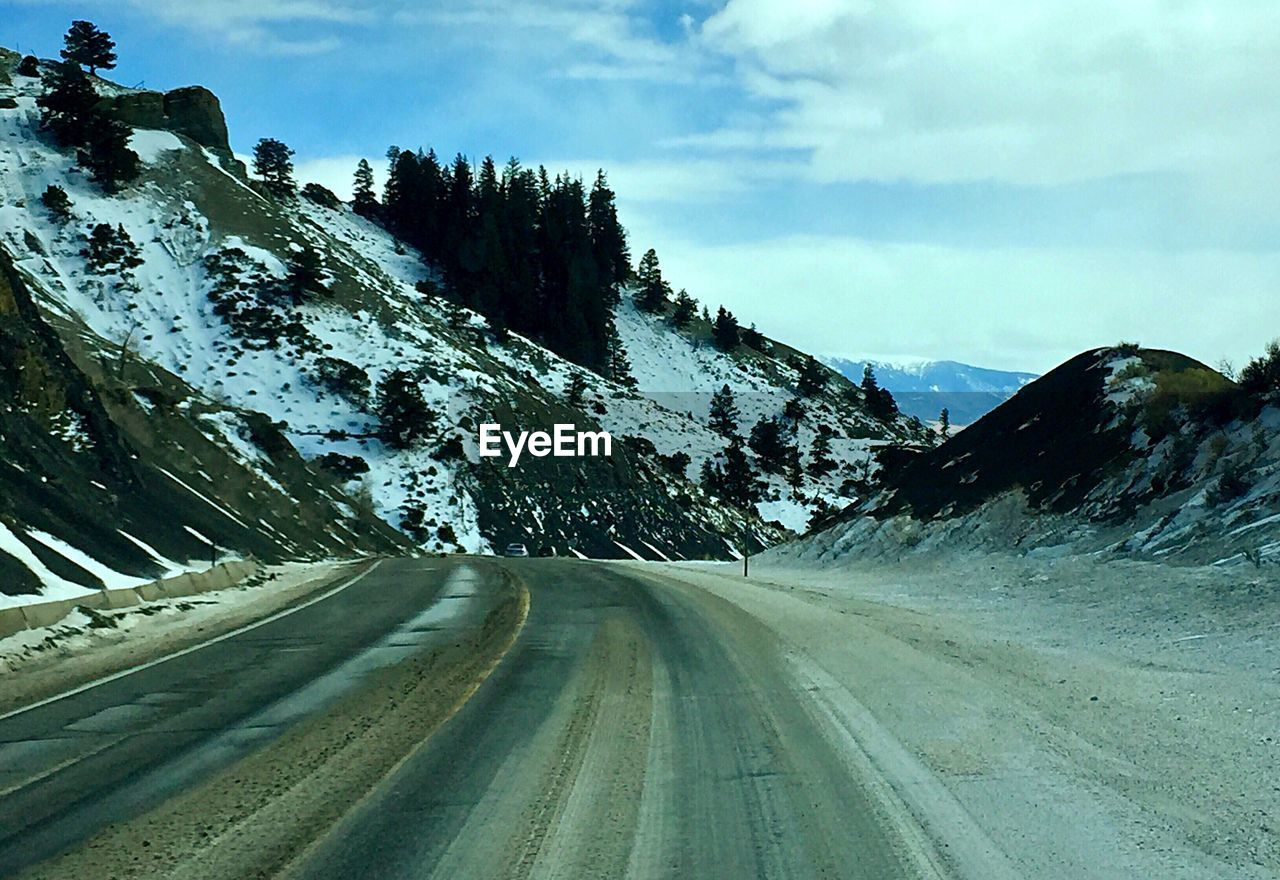 road, sky, transportation, direction, the way forward, cloud - sky, mountain, beauty in nature, no people, cold temperature, diminishing perspective, nature, winter, snow, day, scenics - nature, non-urban scene, empty road, tranquil scene, outdoors