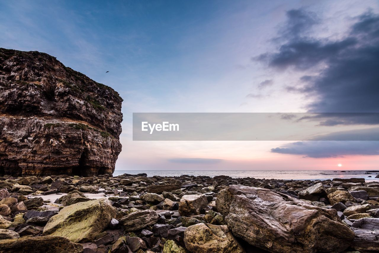 Rock Formation By Sea Against Sky During Sunset