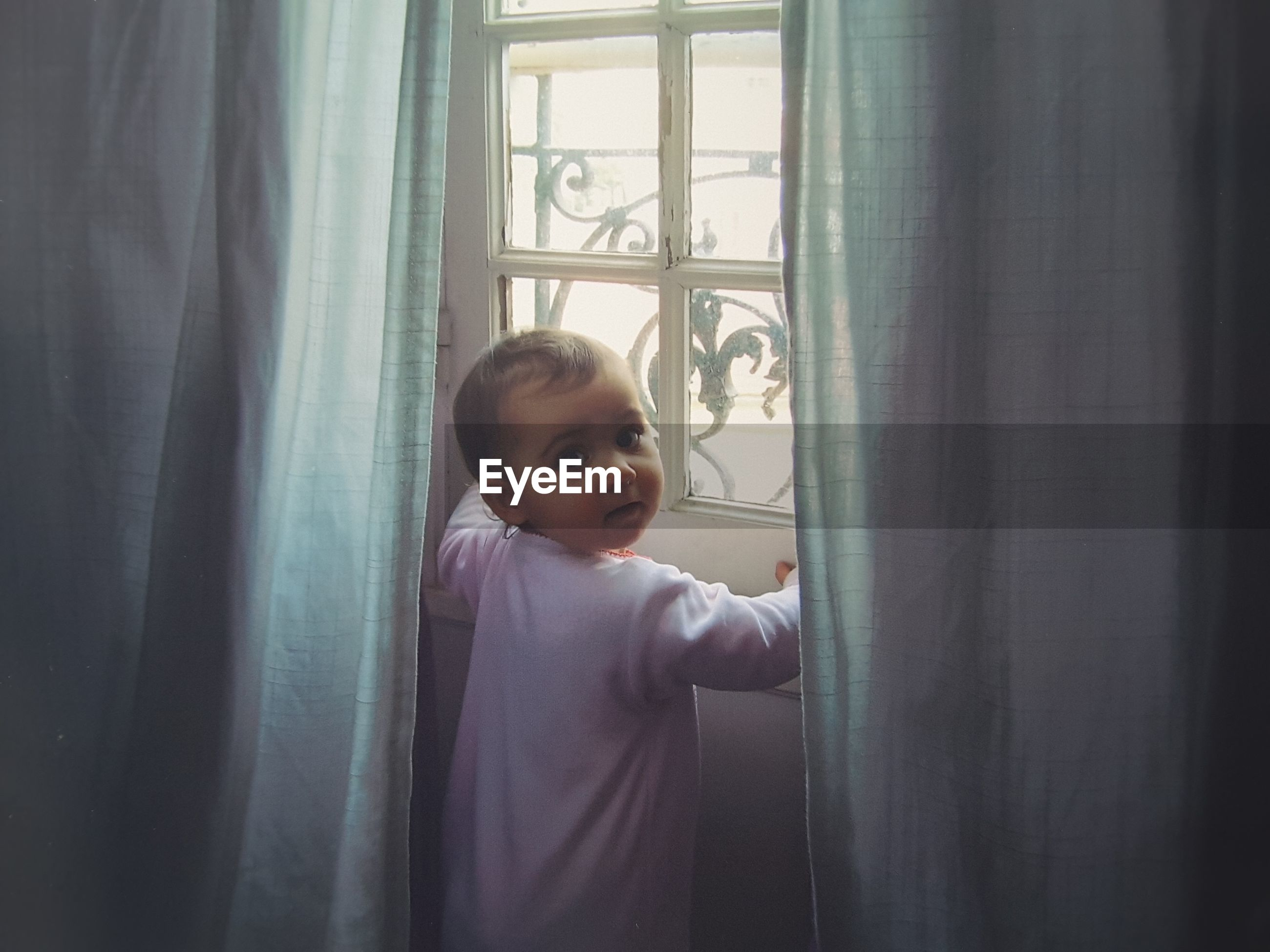 Portrait of cute baby girl standing by window at home
