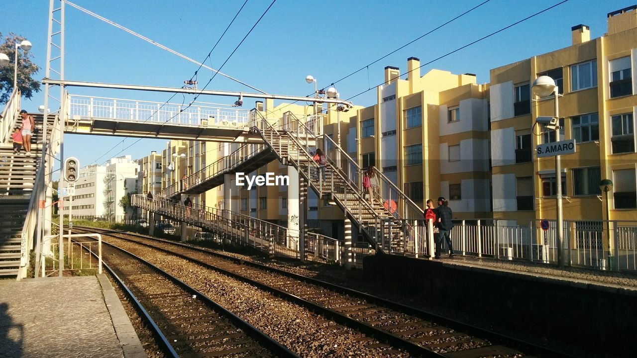 railroad track, transportation, rail transportation, cable, architecture, built structure, train - vehicle, public transportation, day, no people, building exterior, mode of transport, outdoors, sky, clear sky, city
