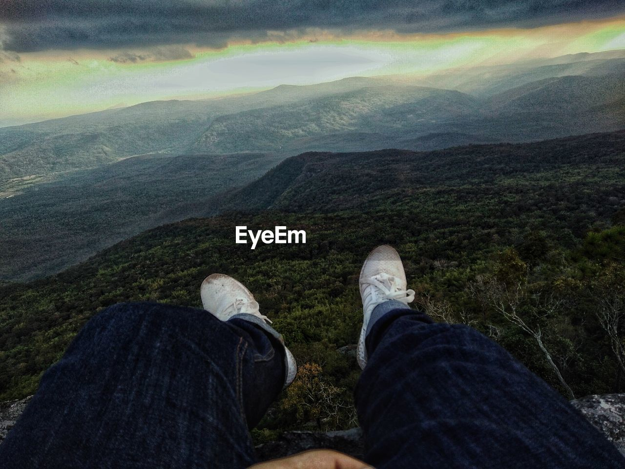 low section, human leg, personal perspective, mountain, one person, body part, scenics - nature, real people, beauty in nature, human body part, shoe, leisure activity, lifestyles, nature, unrecognizable person, day, environment, landscape, tranquil scene, outdoors, jeans, human limb