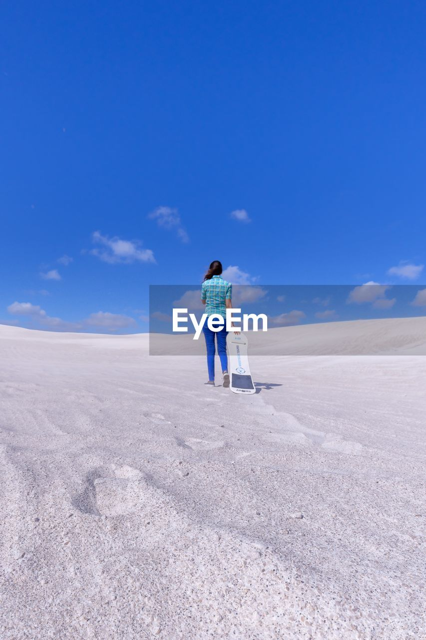 sky, one person, full length, leisure activity, real people, blue, lifestyles, scenics - nature, land, standing, nature, beauty in nature, day, tranquil scene, rear view, non-urban scene, sand, casual clothing, tranquility, outdoors, salt flat, arid climate