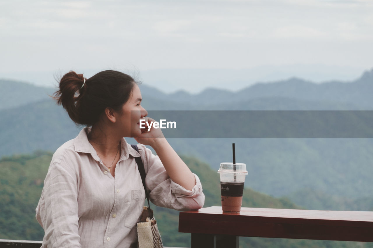 WOMAN LOOKING AT CAMERA ON TABLE AGAINST MOUNTAIN