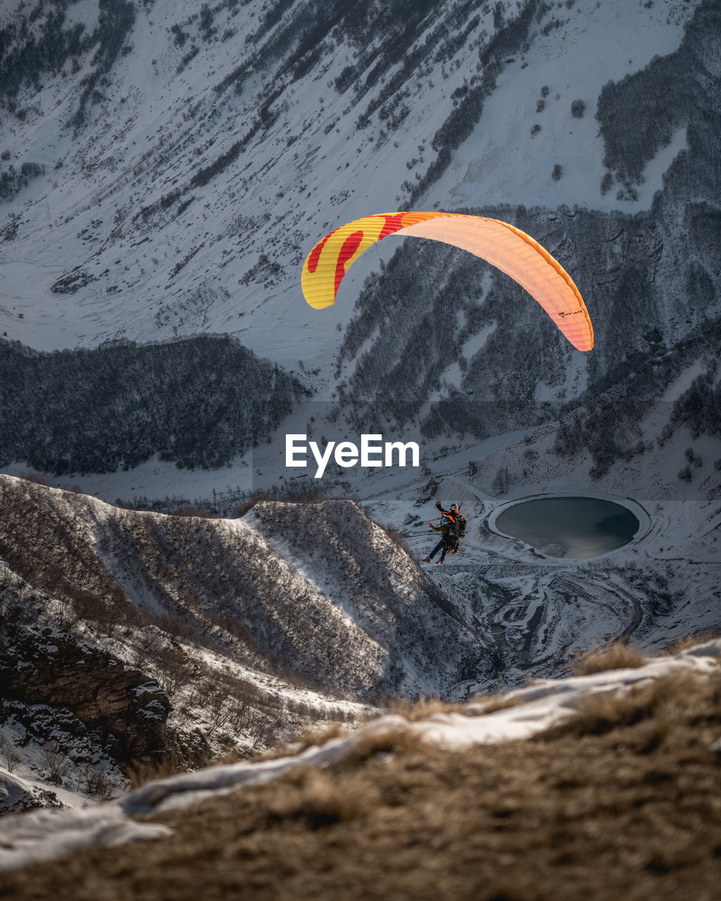 Low angle view of person paragliding against mountain