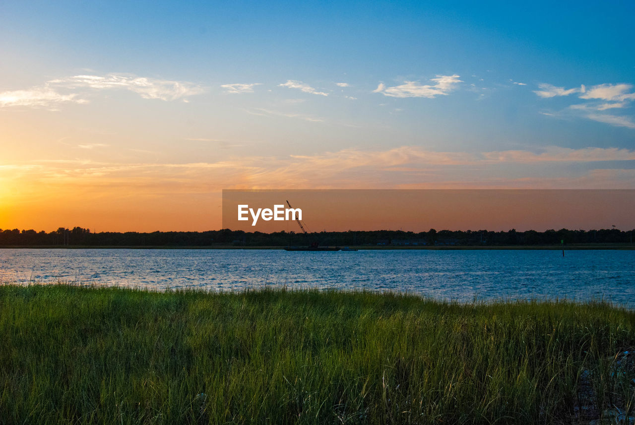 Grassy Field And Lake Against Sky During Sunset