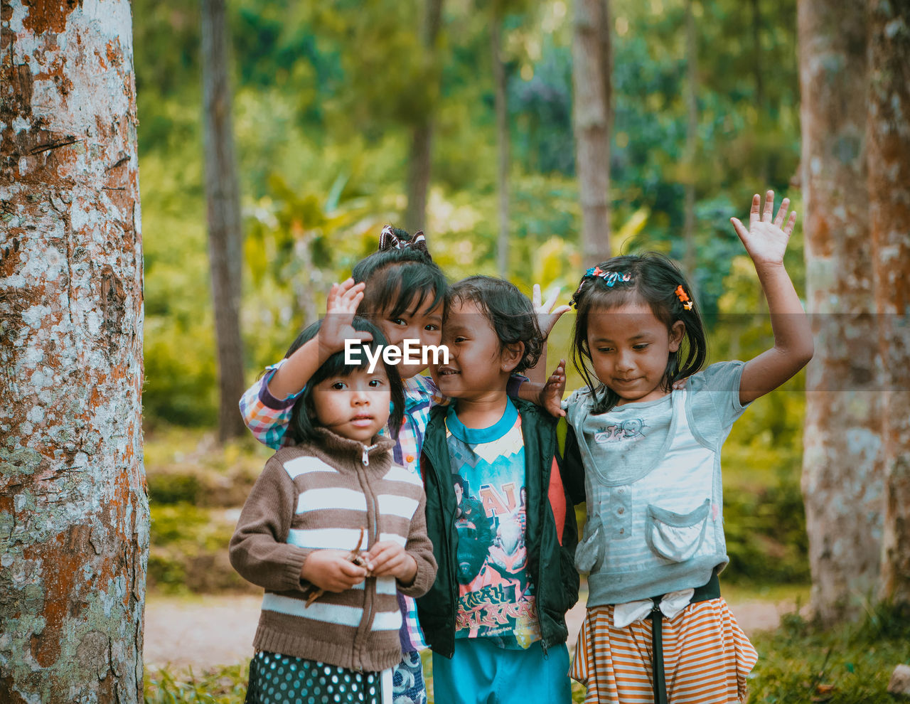 childhood, standing, looking at camera, boys, friendship, day, girls, child, outdoors, casual clothing, children only, togetherness, leisure activity, tree, portrait, smiling, happiness, group of people, real people, nature, people, human body part, adult