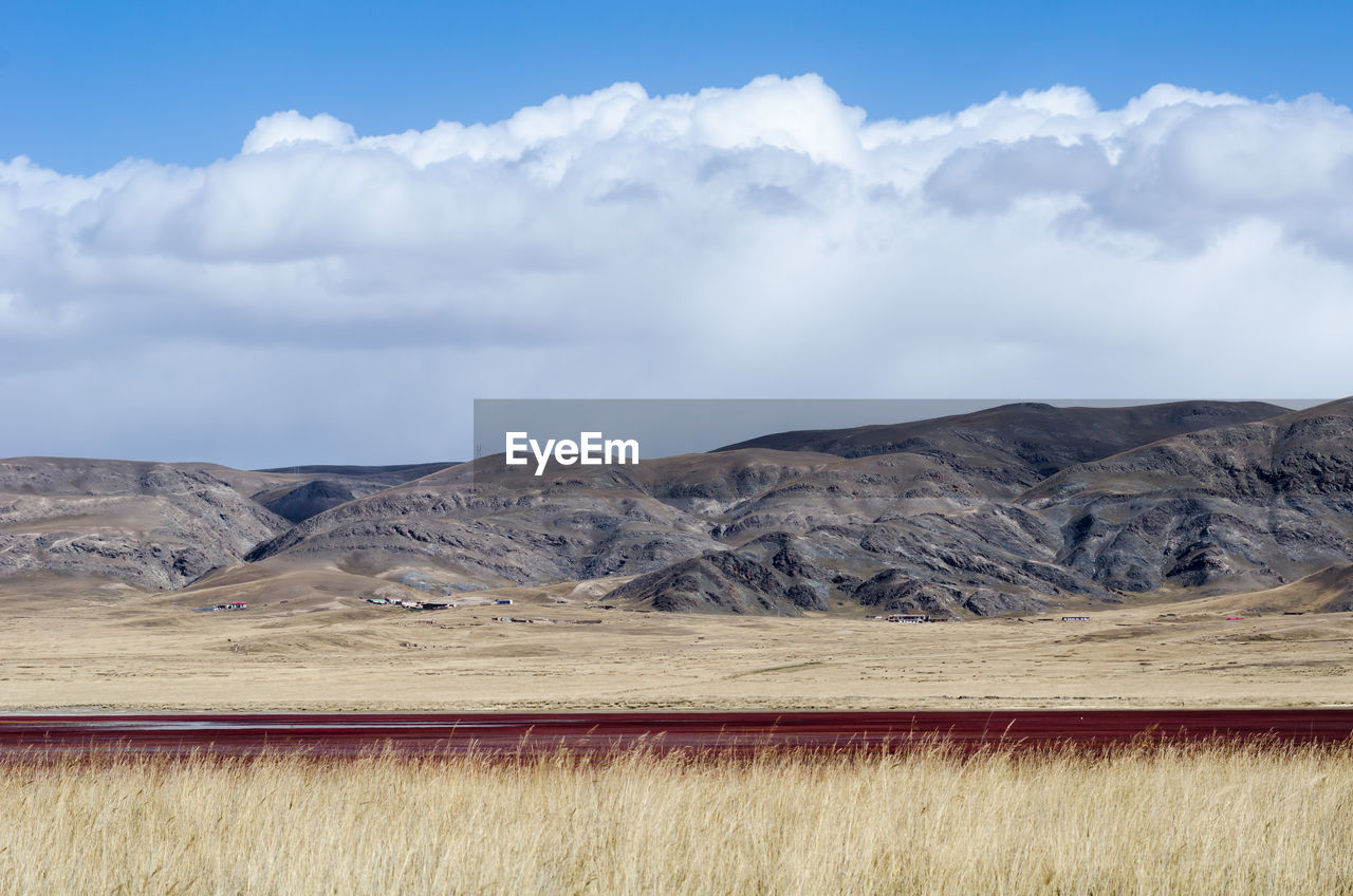 SCENIC VIEW OF ARID LANDSCAPE AND MOUNTAINS AGAINST SKY