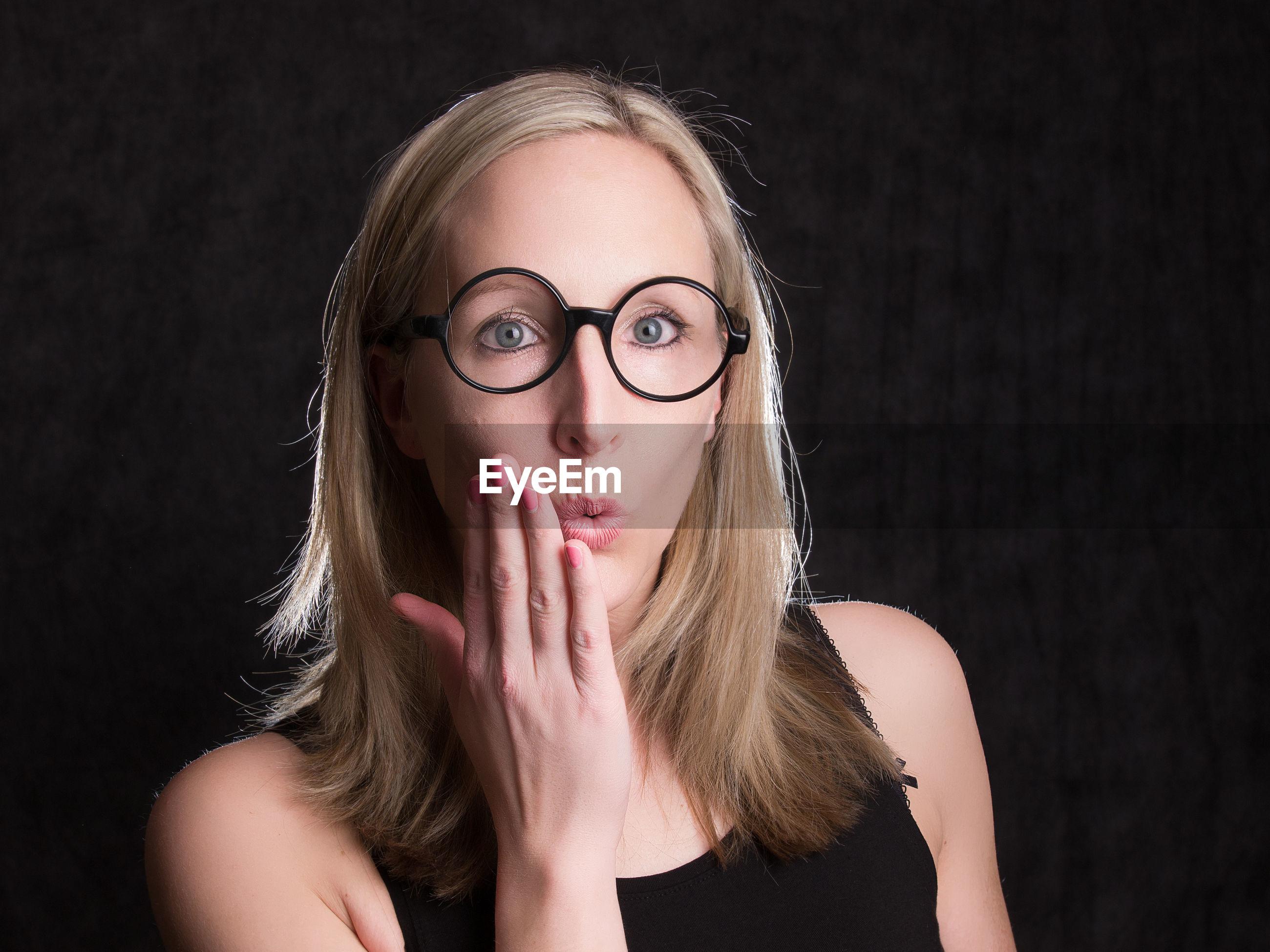 Portrait of shocked woman against black background