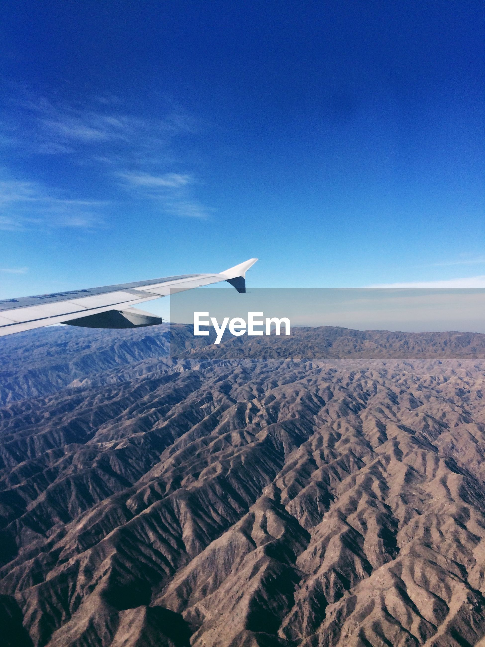 Cropped image of airplane flying above rocky mountains