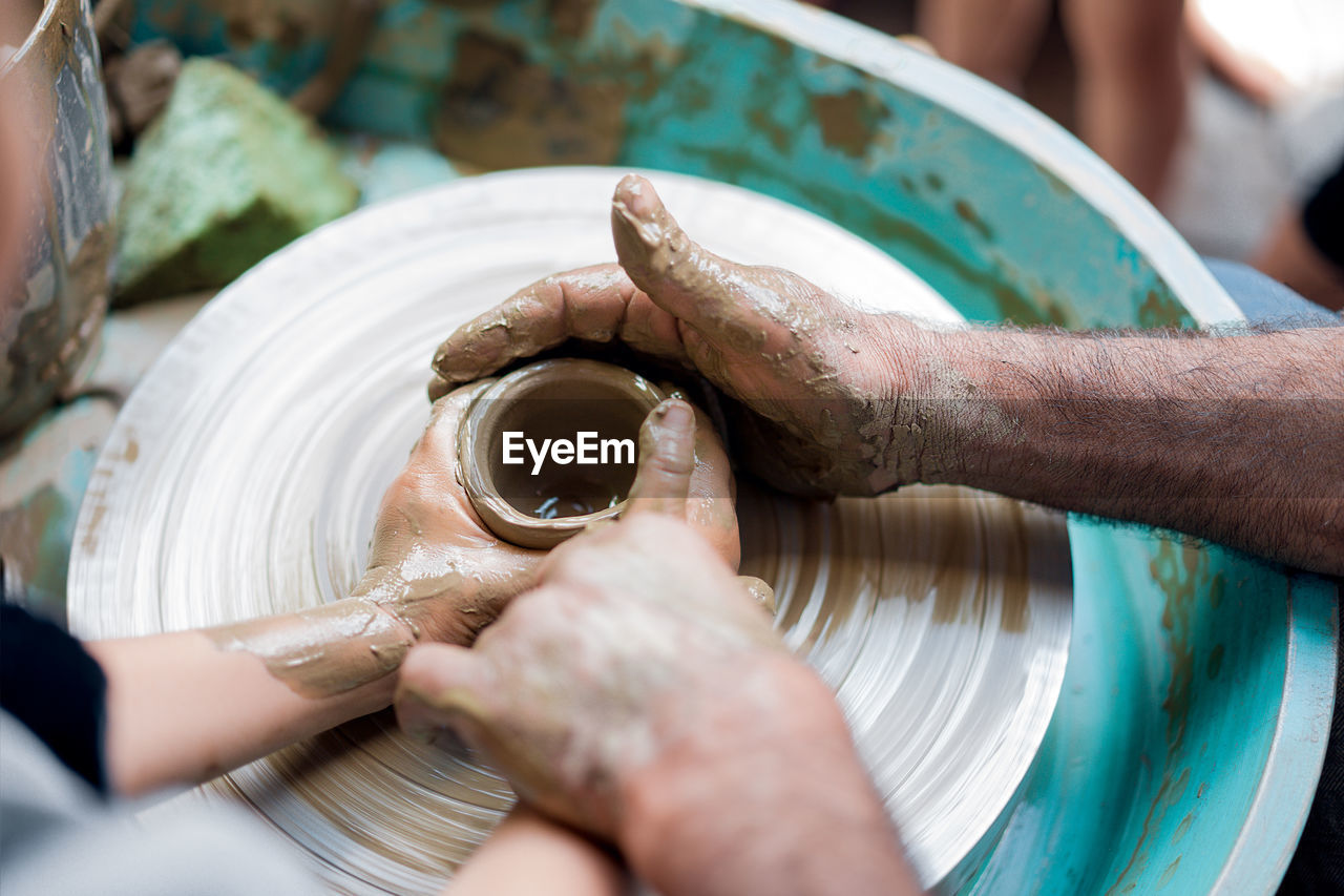 High Angle View Of Man Teaching Child Pottery