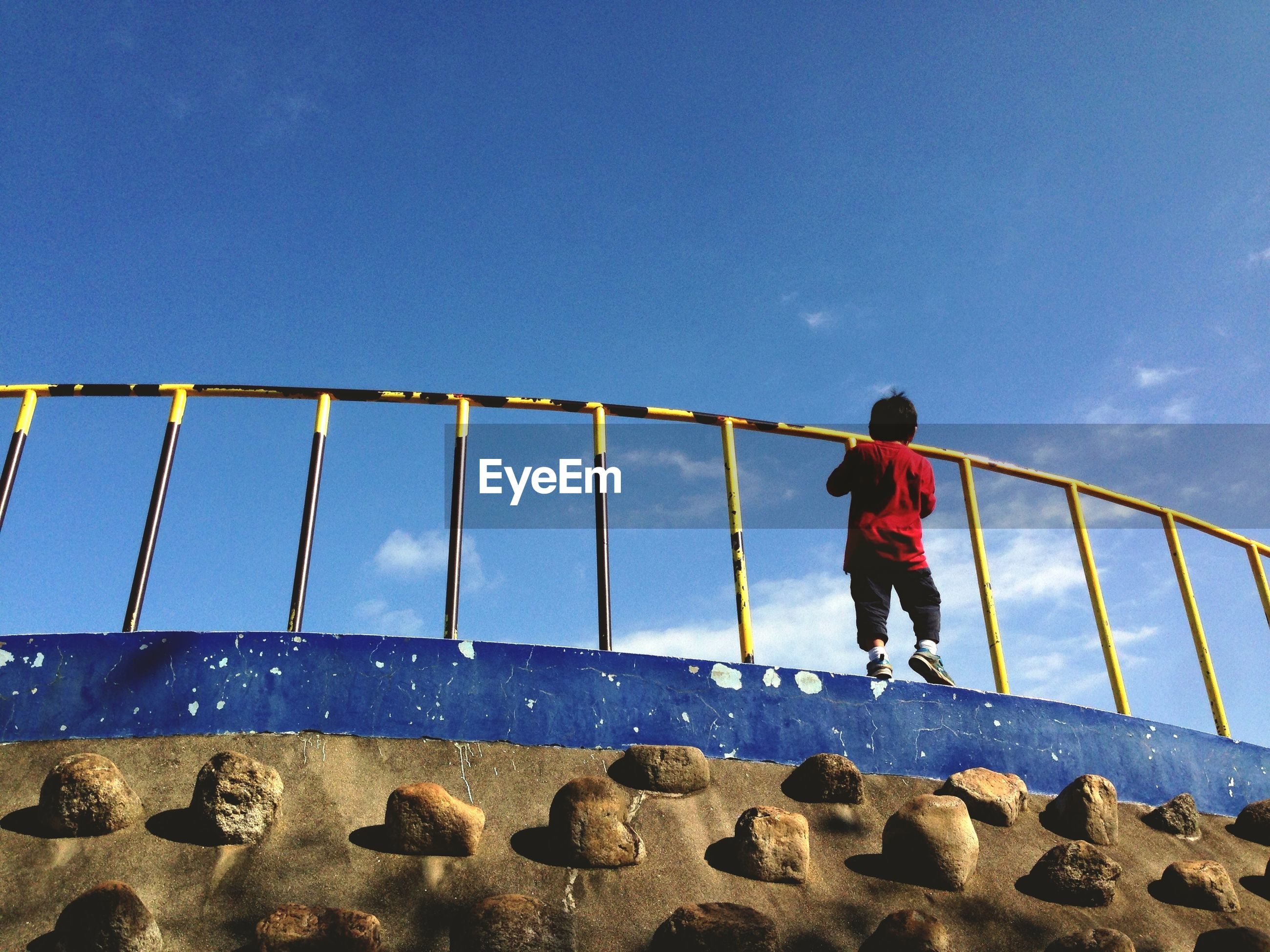 Low Angle View Of Boy On Railing Against Blue Sky